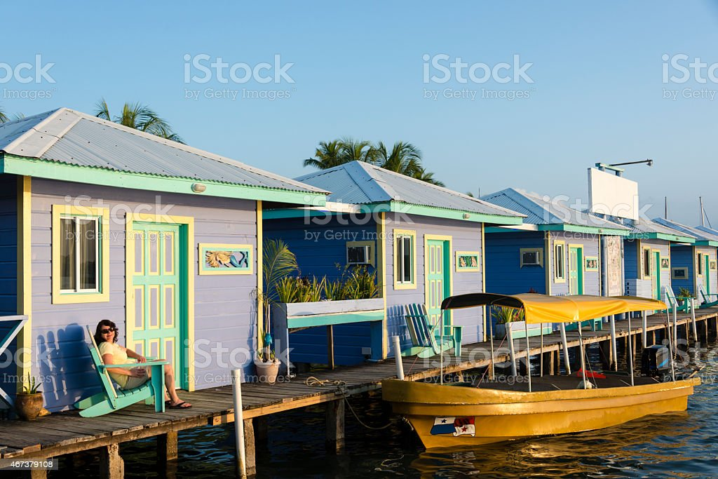 XXXL: Woman relaxing while on vacation in front of bungalow stock photo
