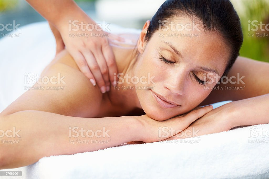 Woman relaxing while receiving a massage royalty-free stock photo