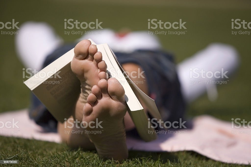 woman relaxing with a book resting over her feet royalty-free stock photo