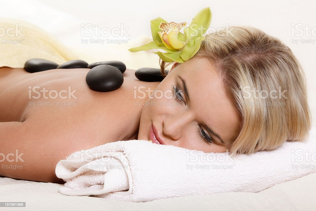 Woman relaxing with flower and hot stones royalty-free stock photo