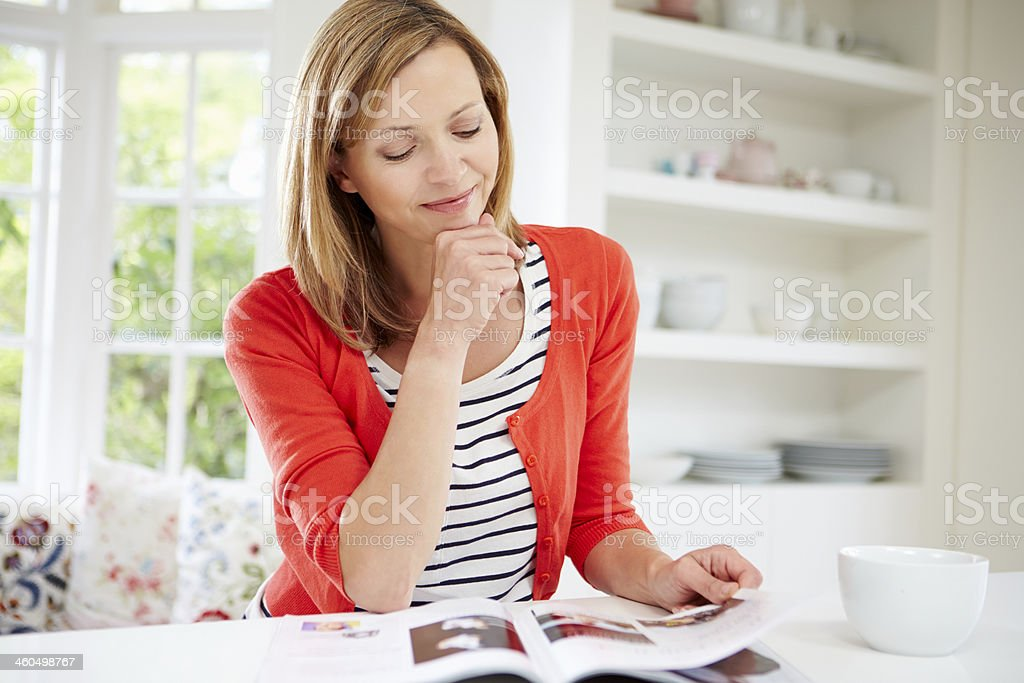 Woman Relaxing With Magazine At Home stock photo