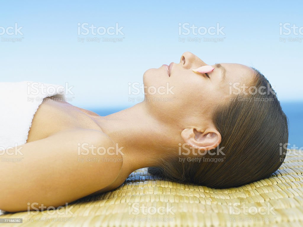 Woman relaxing with rose petals on her eyes royalty-free stock photo