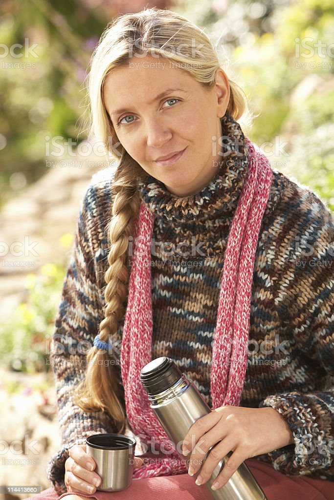 Woman Relaxing With Thermos Flask In Countryside royalty-free stock photo