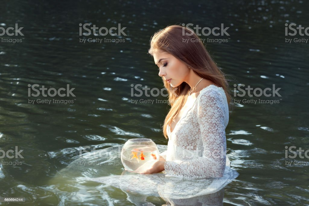 Woman releases a goldfish. stock photo