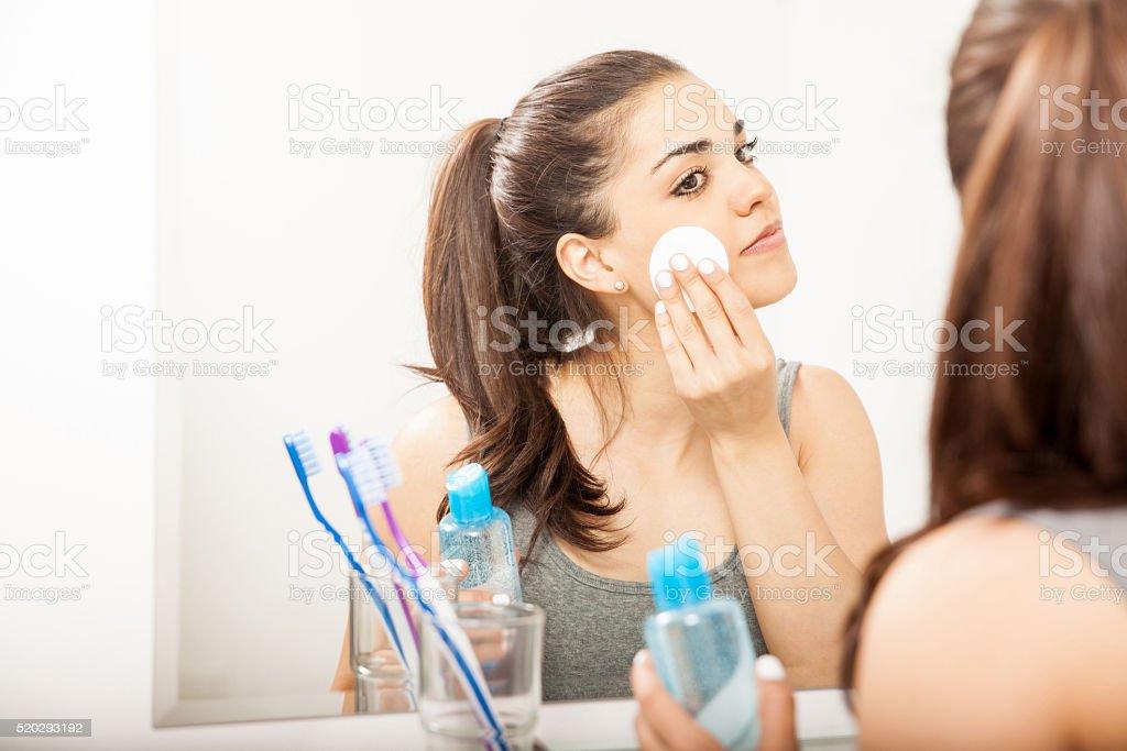 Woman removing makeup at night stock photo