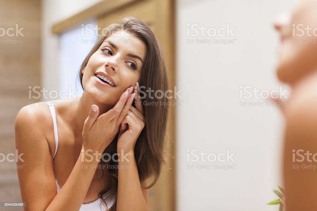 Woman removing pimple from her face stock photo