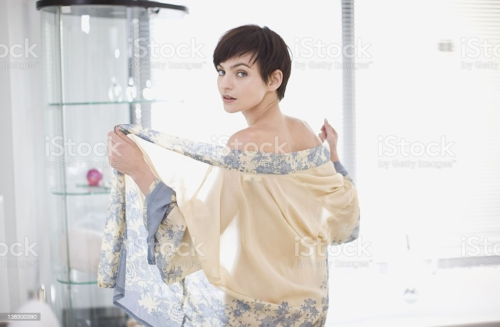 Woman removing sheer robe in bathroom stock photo