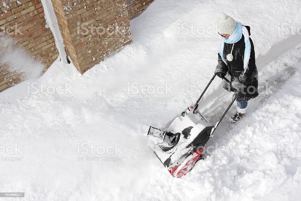 Woman removing snow with a snowblower stock photo