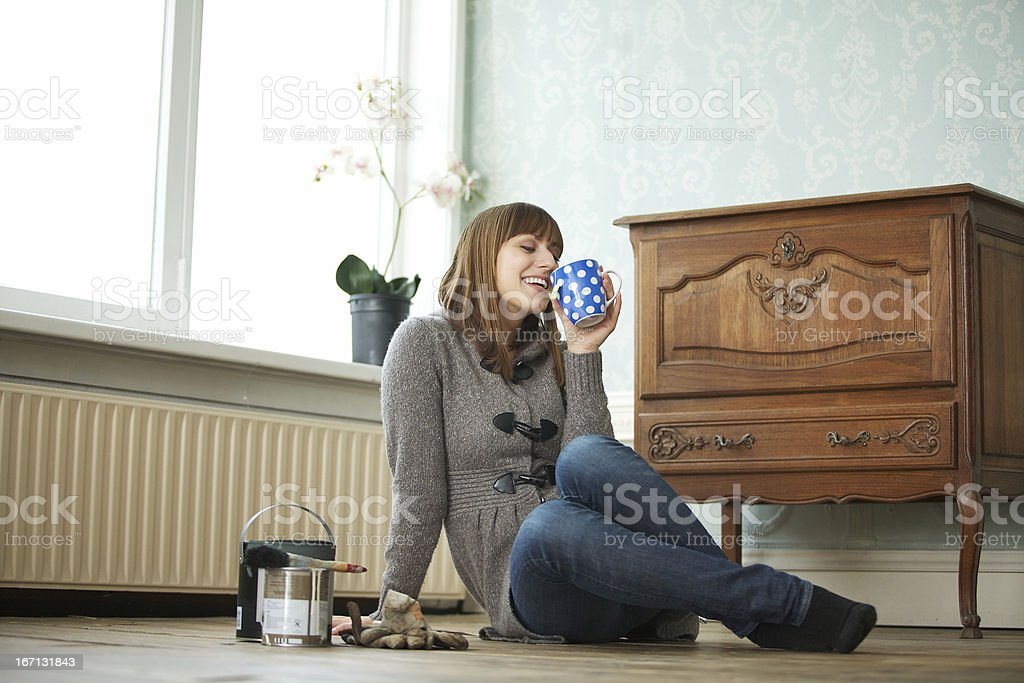 Woman Renovating her Home and Relaxing with Cup of Tea stock photo