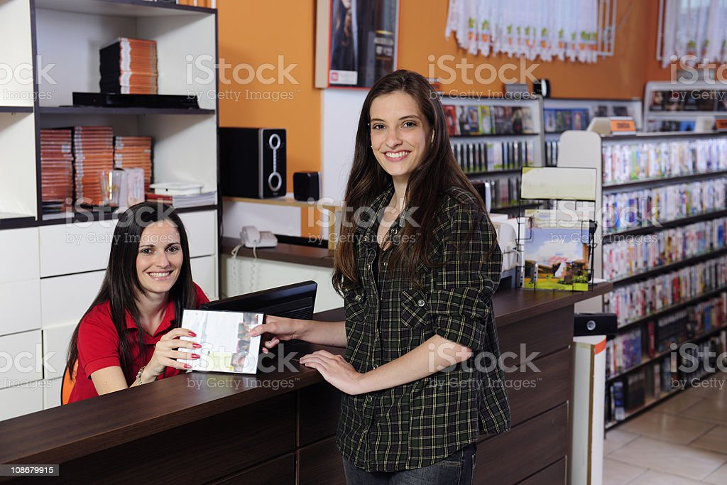 woman renting a DVD at the video store stock photo