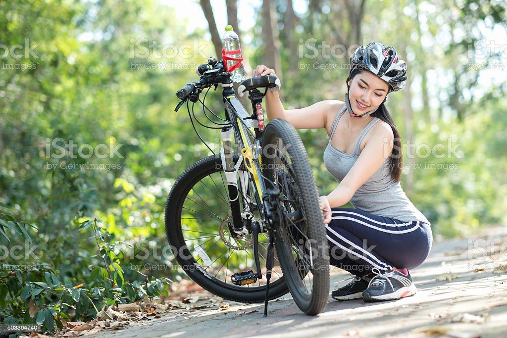 Woman repairing bicycle stock photo