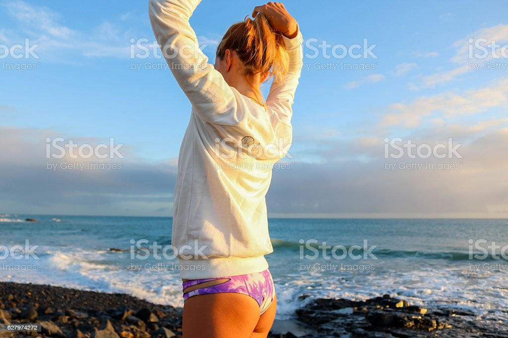 Woman repearing her hair by the beach stock photo