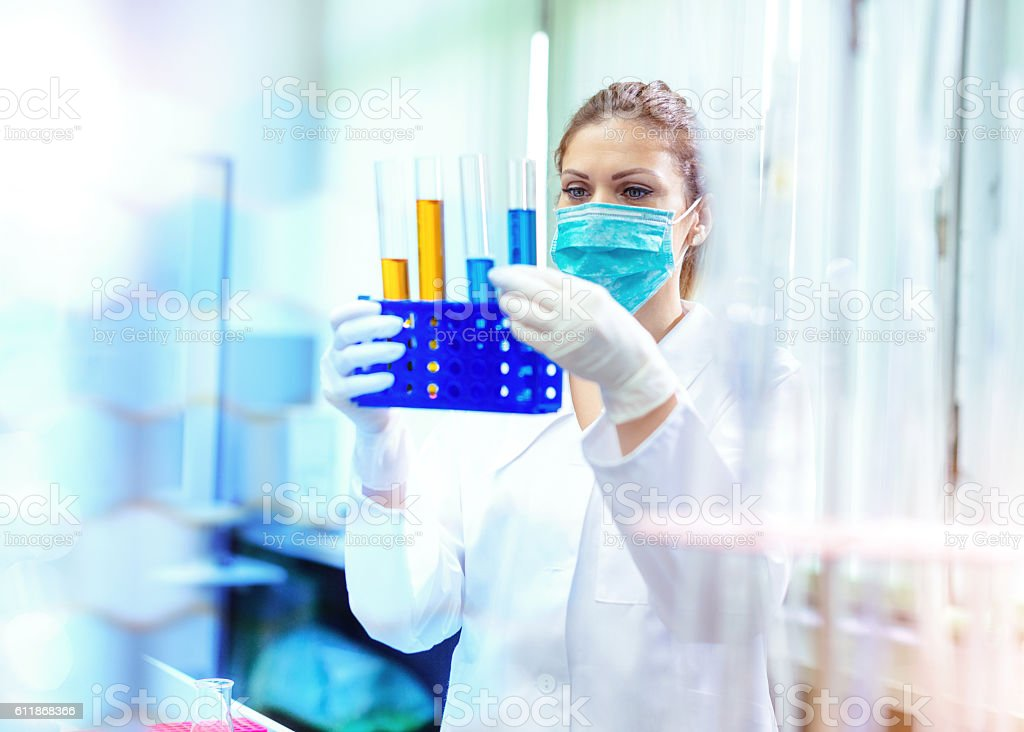 Woman researcher examining liquids and solutions in laboratory stock photo