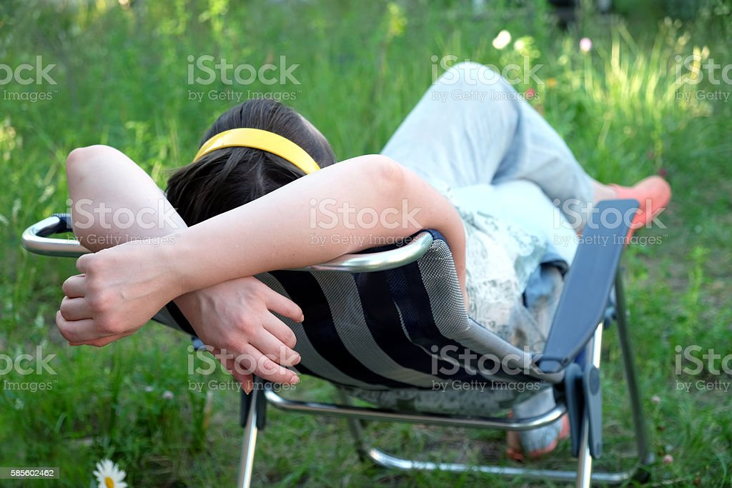 Woman rest on folding deck chair on meadow stock photo
