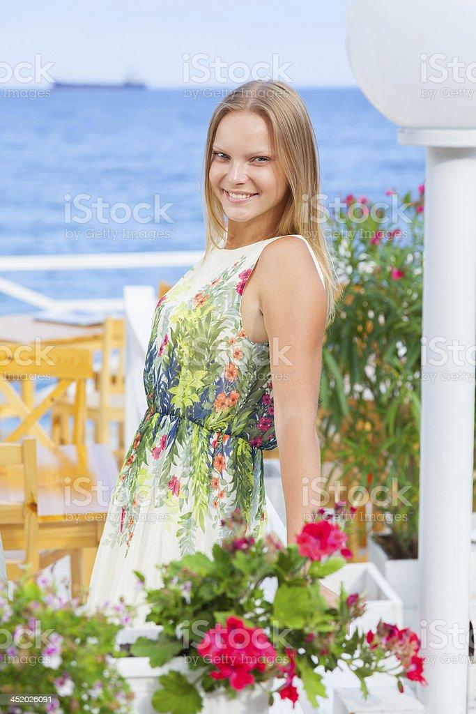 Woman resting at cafe near sea smiling enjoying summer vacation royalty-free stock photo