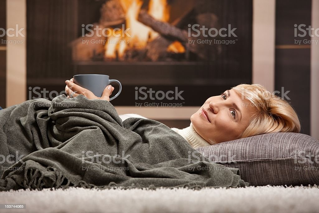 Woman resting beside fireplace royalty-free stock photo