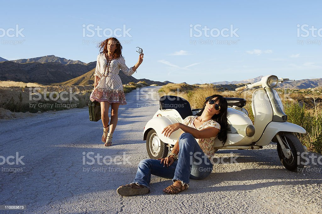 Woman resting by road with motorbike stock photo