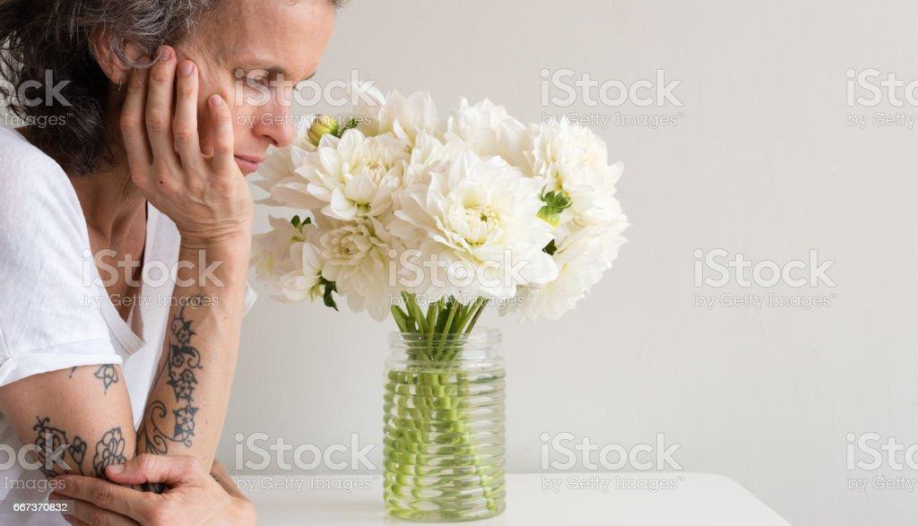 Woman resting near white dahlias stock photo