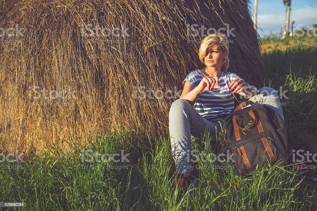 Woman resting next to  a stack of hay stock photo