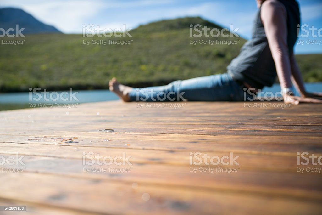 Woman resting on a wooden deck overlooking a dam stock photo