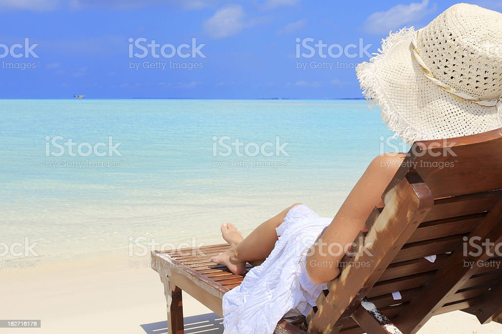 Woman resting on deck chair at the tropical beach royalty-free stock photo