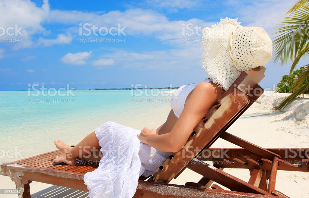 Woman resting on deck chair at the tropical beach. royalty-free stock photo
