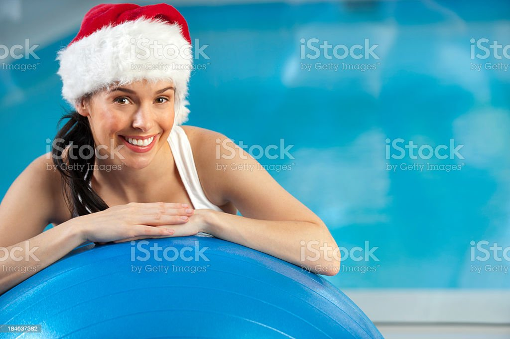 Woman resting on exercise ball with Santa hat royalty-free stock photo