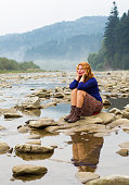 woman resting on the rocks in the middle of mountain lake
