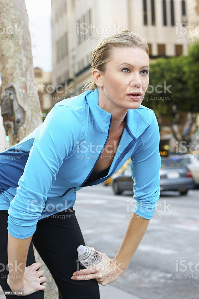 Woman Resting Whilst Running Along Street royalty-free stock photo