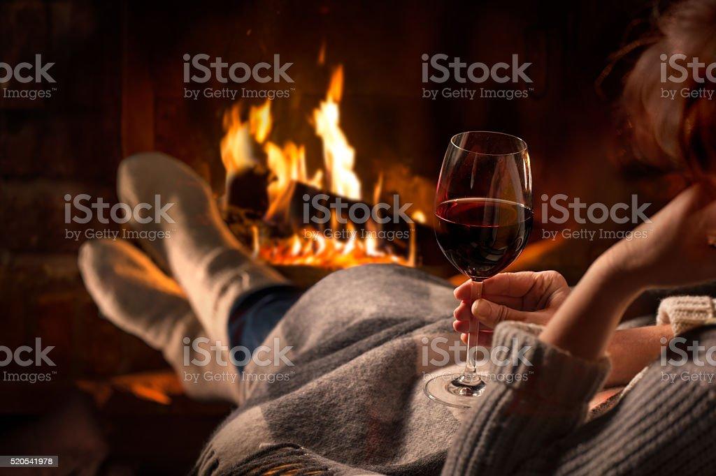 Woman resting with wine glass near fireplace stock photo