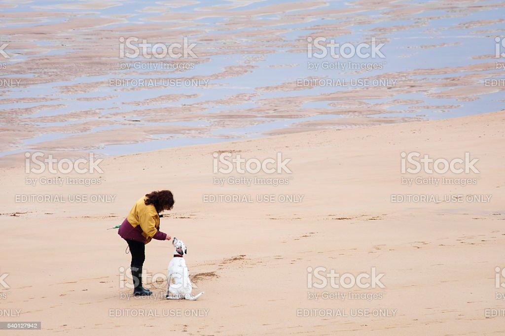 Woman rewarding her dog on San Lorenzo beach, Gijón. stock photo