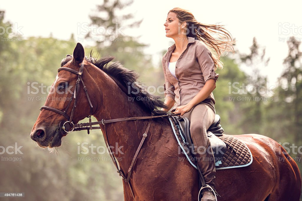 Woman ridding a stallion in nature. stock photo