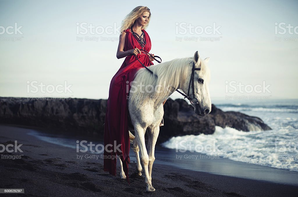 Woman rides along the beach on a horse stock photo