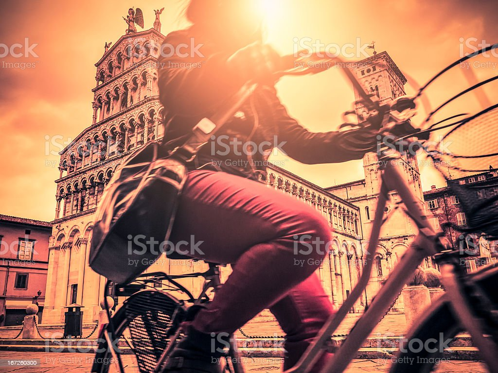 Woman riding a bicycle in Lucca against the cathedral royalty-free stock photo