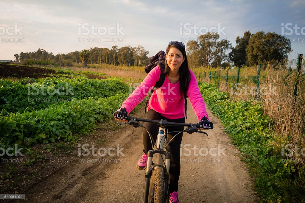 Woman riding a bicycle in the countryside stock photo