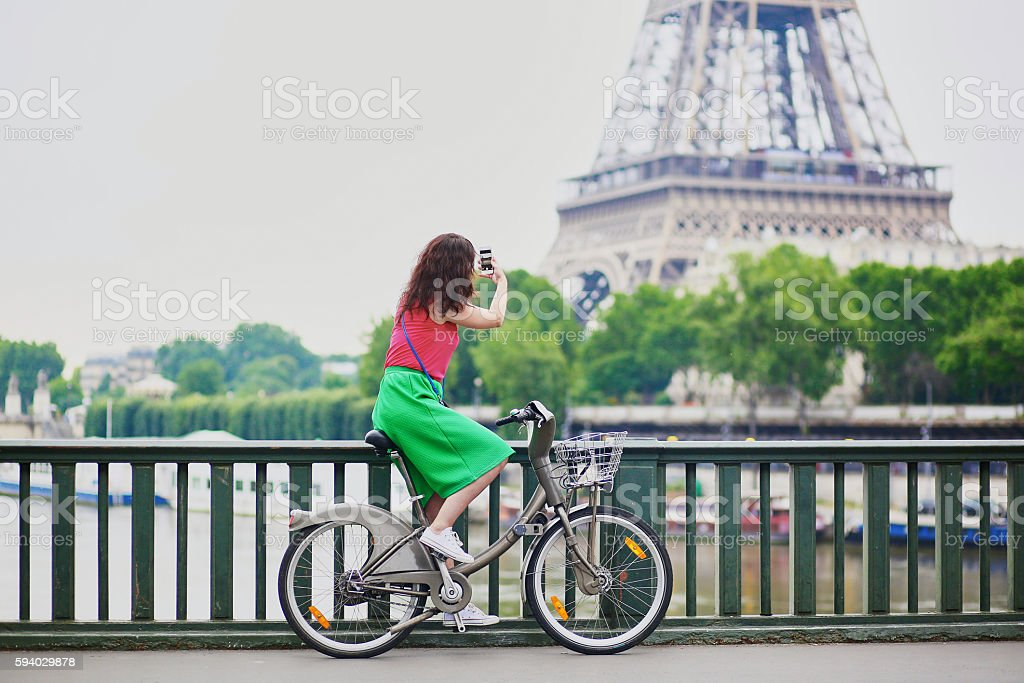 Woman riding a bicycle on a street of Paris stock photo