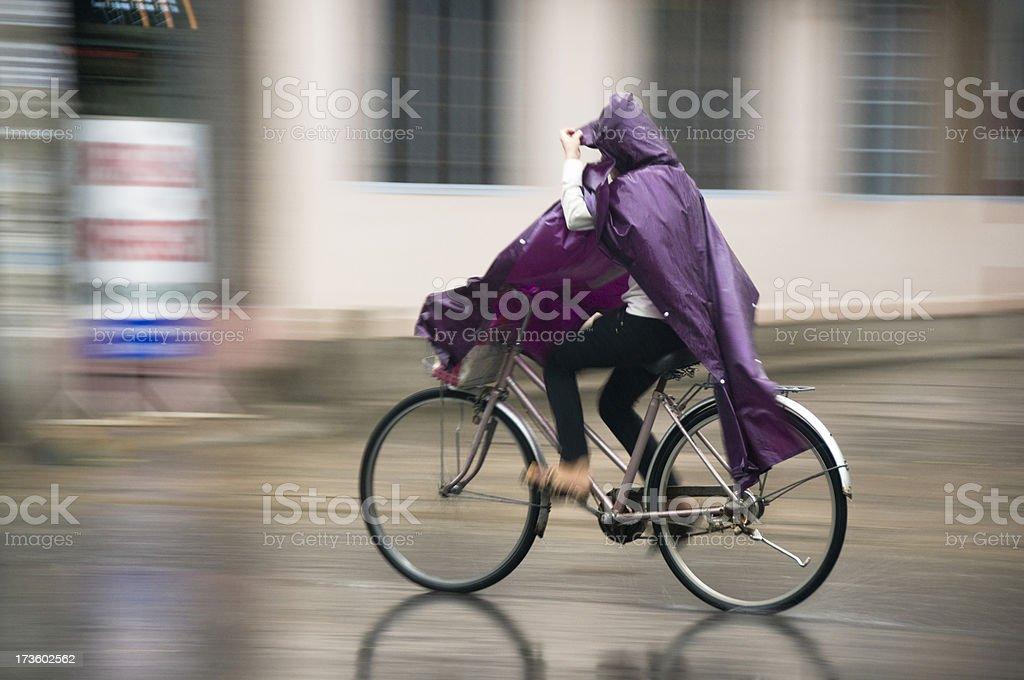 Woman Riding A Bicycle Through The Rain In Nha Trang stock photo