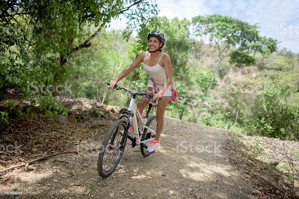 Woman riding a bicycle up in the mountains stock photo