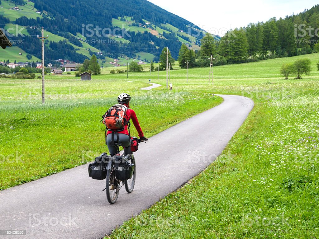 Woman riding a bike along river Drava in Austria stock photo