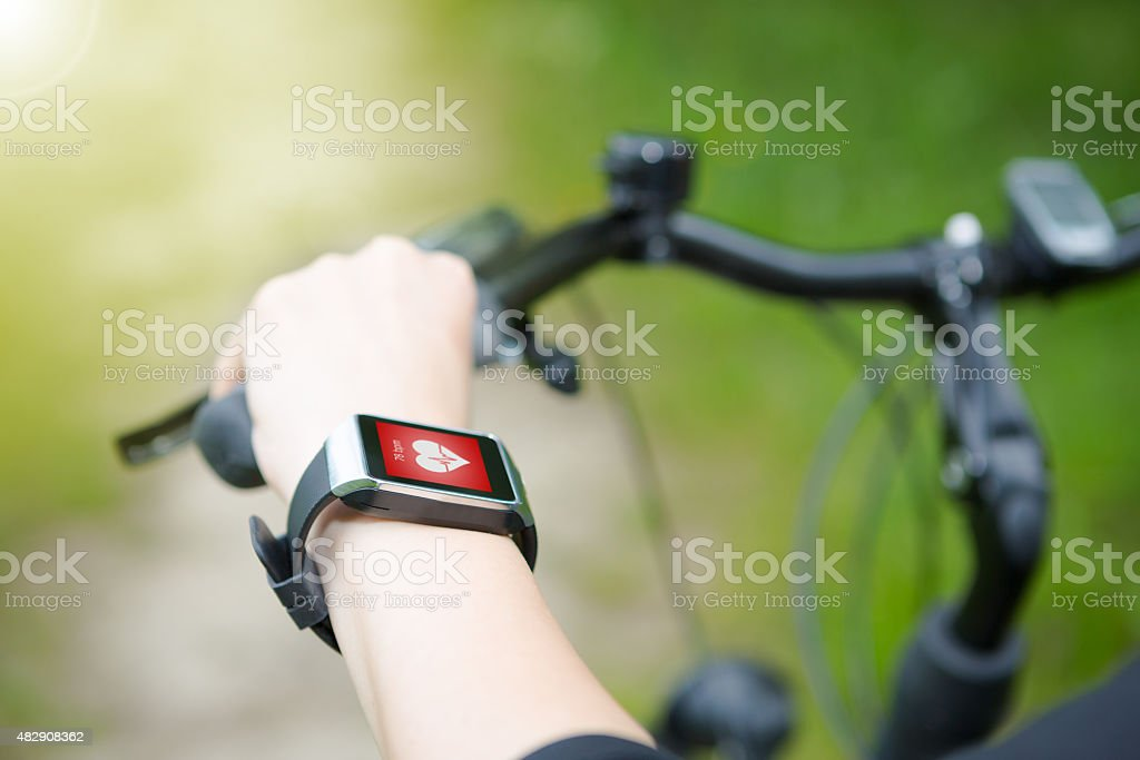 Woman riding a bike with a smartwatch heart rate monitor. stock photo