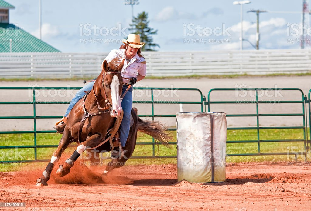 Woman riding a brown horse in a barrel race  stock photo