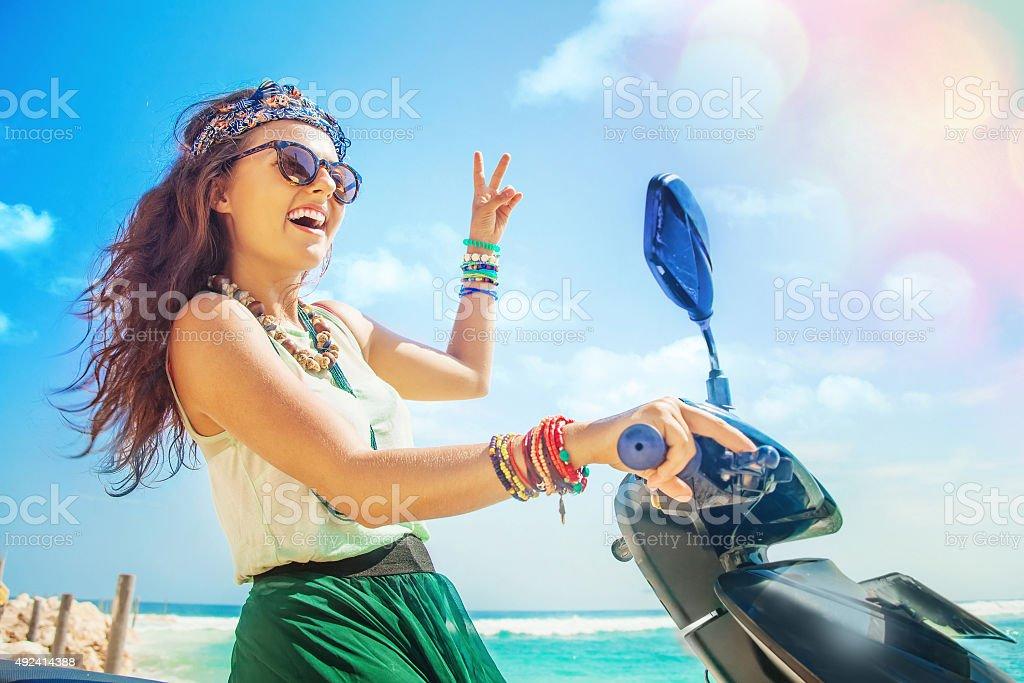 Woman riding a motorbike along beach stock photo