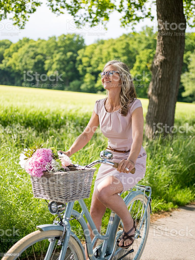Woman riding a vintage bicycle through a summer park stock photo