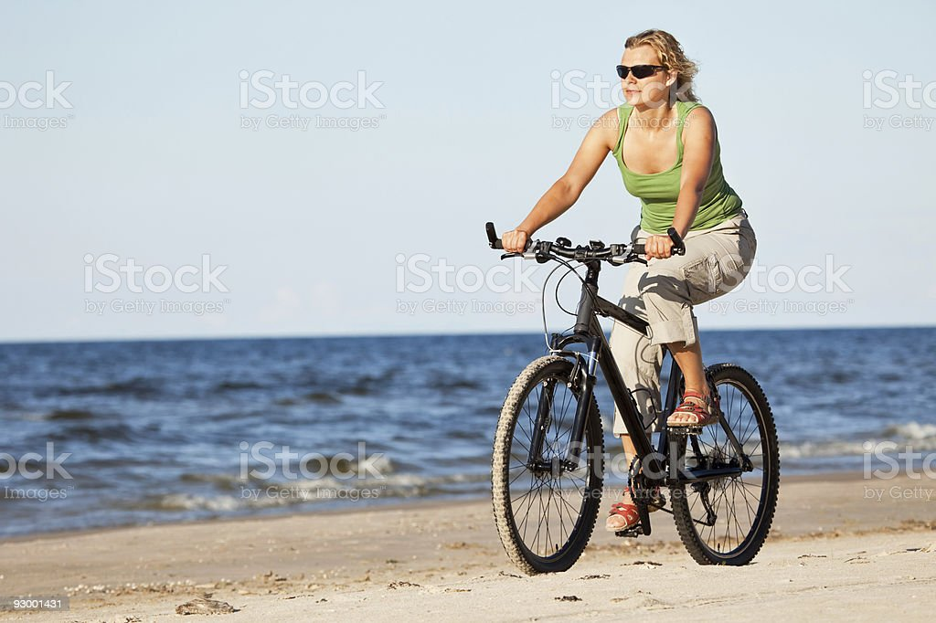 Woman riding bicycle in beach royalty-free stock photo