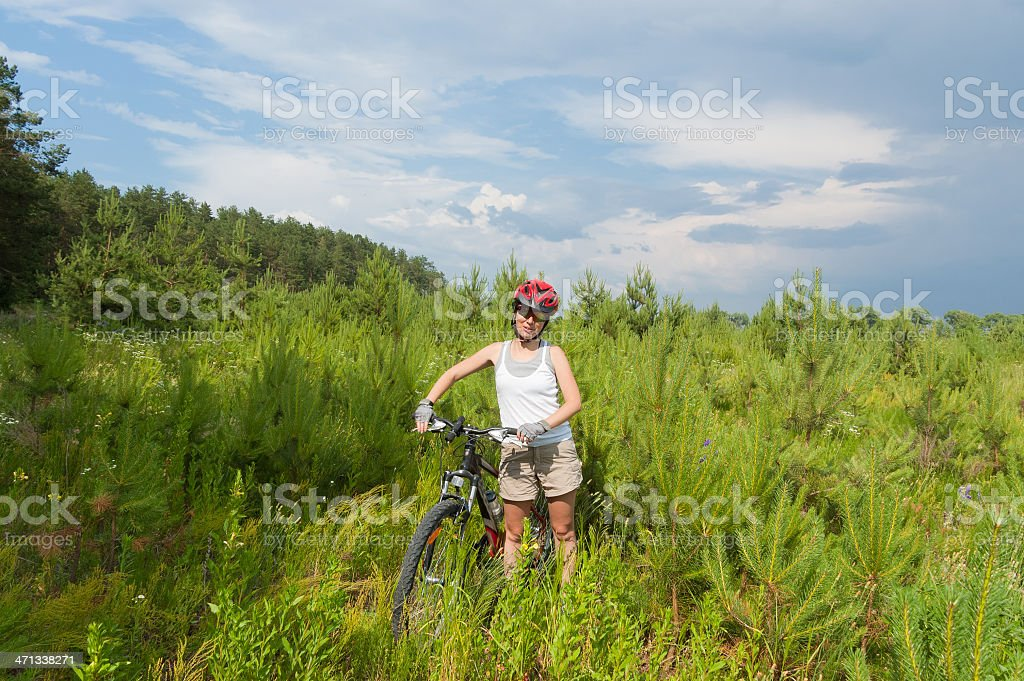 Woman riding bicycle in forest stock photo