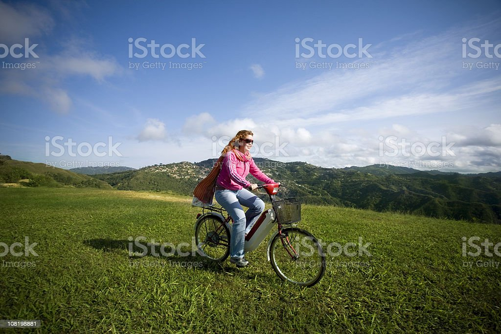 Woman Riding Bicycle in Meadow Field with Valley Background royalty-free stock photo