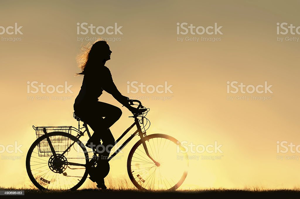 Woman Riding Bicycle Silhouette stock photo