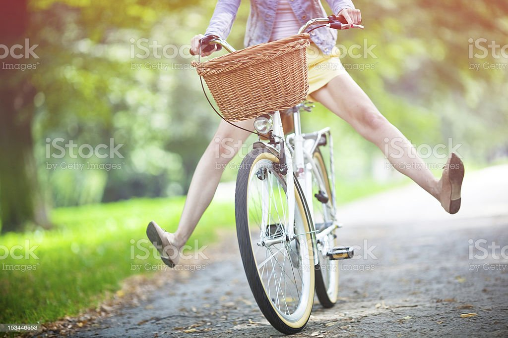 Woman riding bicycle with her legs in the air stock photo