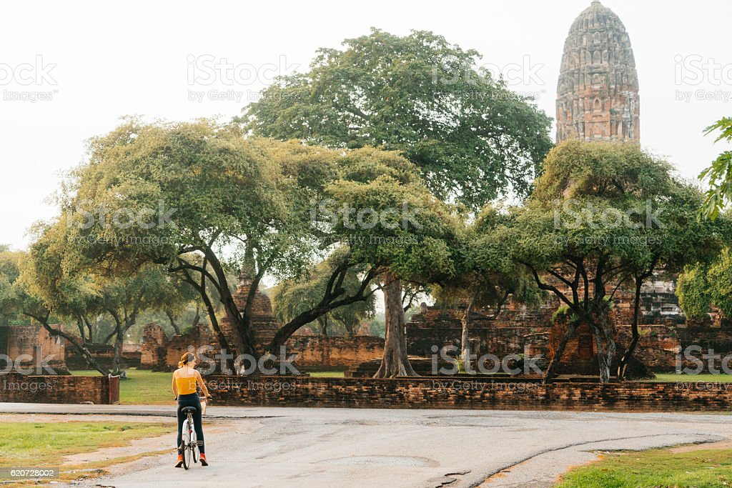 Woman riding bike near ancient Buddhist Temples stock photo