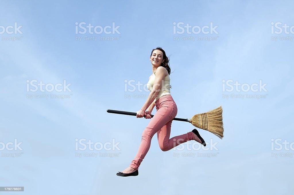 woman riding broom stock photo